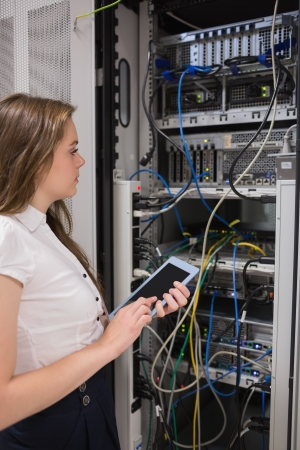 Woman with a  tablet pc looking at the servers in data center photo