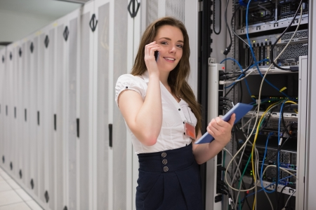 Smiling woman on the phone holding tablet pc and checking servers in data center photo