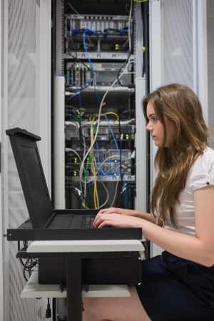 Woman checking the servers in data center photo