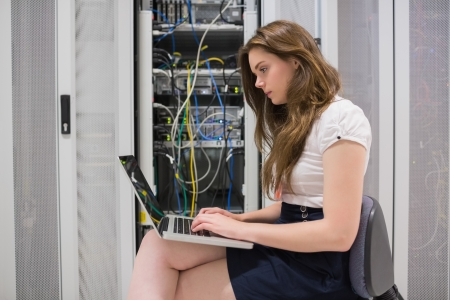 Female technician doing data storage with the laptop in data center Stock Photo - 15593401