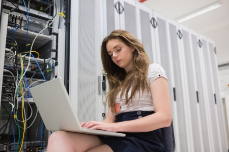 Woman saving data while sitting in the hallway photo