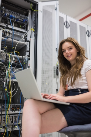 Woman with laptop doing data storage in data center photo