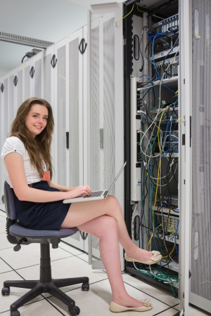 Happy woman with laptop working with servers in data center photo