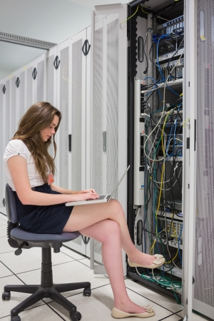 Woman working on laptop with servers in data center photo