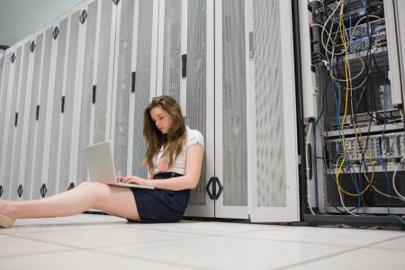 Woman sitting on floor working on laptop in data center photo