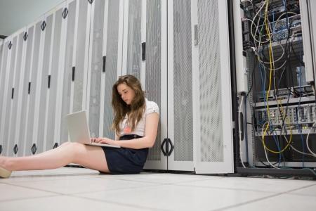 Woman sitting on floor working on laptop in data center Stock Photo - 15584345
