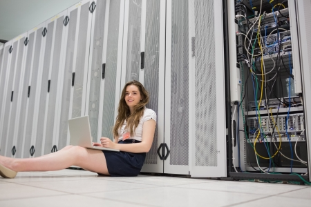 Happy woman sitting on floor working on laptop in data center photo