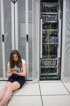 Woman working on servers with tablet pc sitting on floor in data center photo