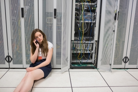 Woman sitting on the floor beside servers on the phone in data center photo