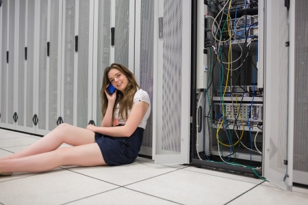 circuitboard: Happy woman sitting beside servers on the phone on the floor of data center