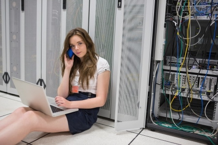 Woman on the phone working with laptop on servers in data center photo