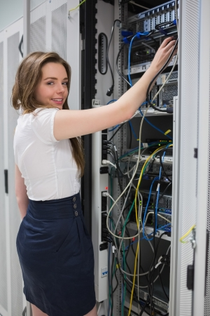 Smiling brunette fixing wires of servcer at the data center photo
