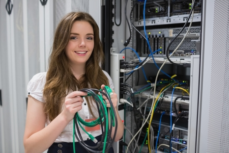 Happy woman holding server wires in data center Stock Photo - 15593509