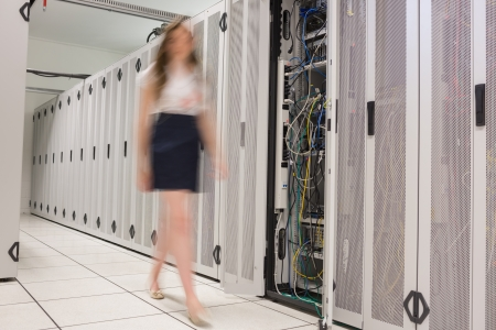 Woman walking through data center beside servers photo