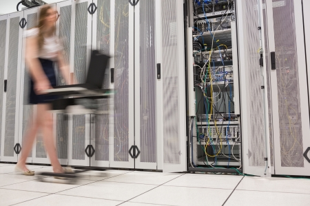 Woman pushing computer through data center beside the servers photo