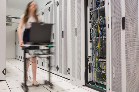 Woman pushing computer to open servers in data center photo