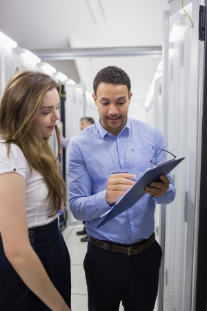 Technicians talking in data center while looking at a clipboard photo
