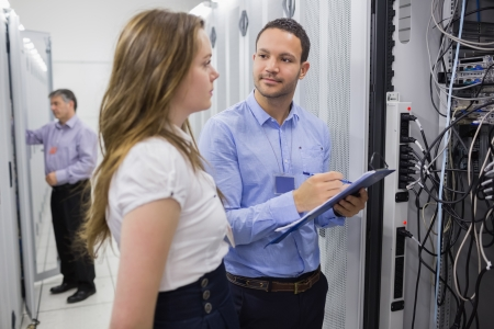 Two people checking servers with one holding clipboard in data center photo