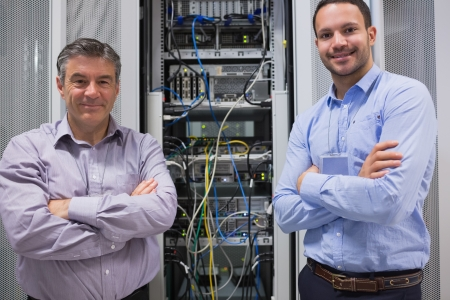 Technicians smiling while standing in front of servers in data center photo