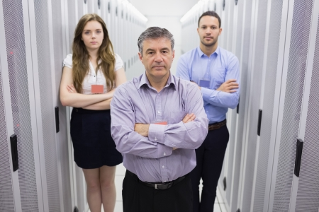 Three people standing in data center with arms crossed looking serious photo
