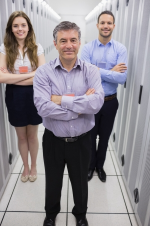 Smiling technicians standing in data center with arms crossed photo