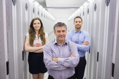 Three smiling people standing in data center with arms crossed photo