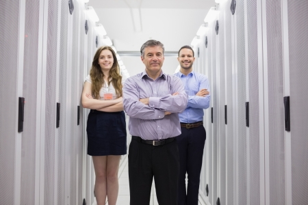 Three smiling technicians standing in data center with arms crossed photo