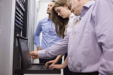 data center: Technicians checking servers with laptop in data center Stock Photo
