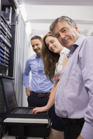 Three happy technicians checking servers with laptop in data center photo