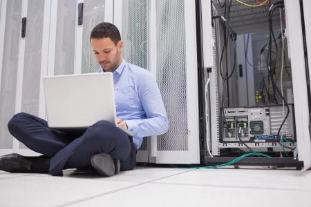 El hombre sentado en el suelo con la computadora portátil al lado de los servidores del centro de datos
