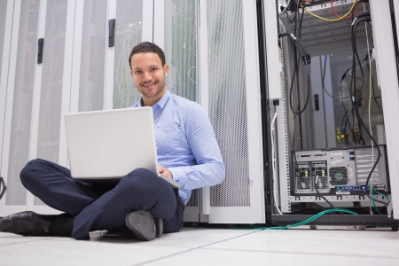 Smiling man sitting on floor checking servers with laptop in data center photo