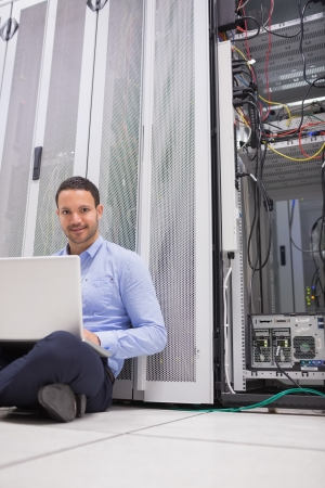Man sitting on floor using laptop to check servers in data center photo