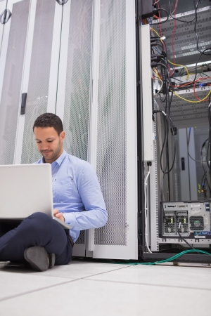 Man working with his laptop on the floor beside servers in data center photo