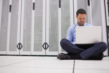 Technician sitting on floor working on laptop in data center photo