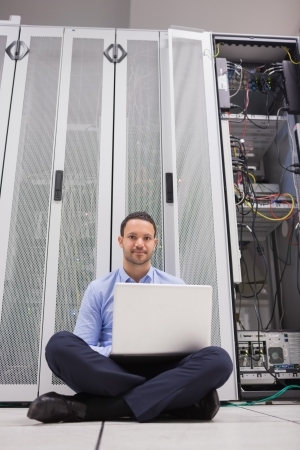 Man sitting in front of servers with his laptop on the floor of data center photo