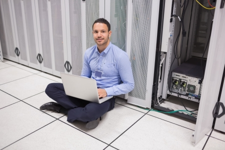 Man sitting on floor beside servers with laptop in data center photo