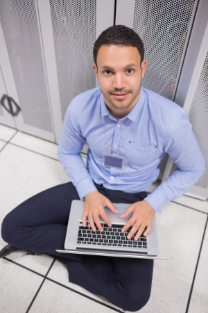 Smiling man using laptop in front of servers of data center photo
