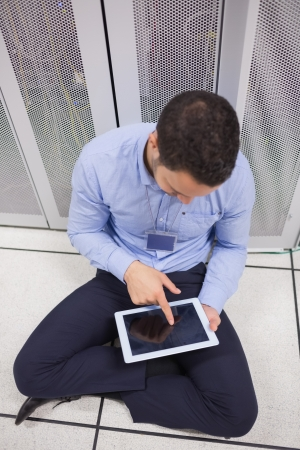 Man using tablet pc in data center sitting on floor photo