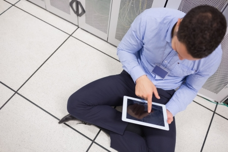 Man with his tablet pc while sitting on the floor in data center photo