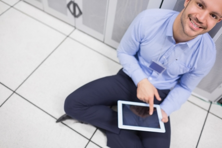 Technician happily using tablet pc in data center sitting on floor photo