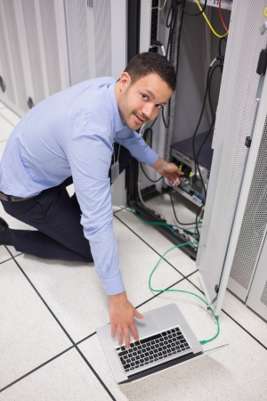 Smiling technician inserting a USB while doing maintenance photo