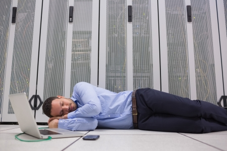 computer centre: Man sleeping while doing maintenance on servers with laptop Stock Photo