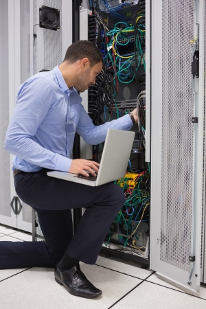 data processor: Man fixing wires while doing maintenance with laptop in data center