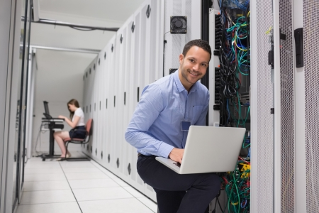 Two technicians doing data storage with their laptops photo