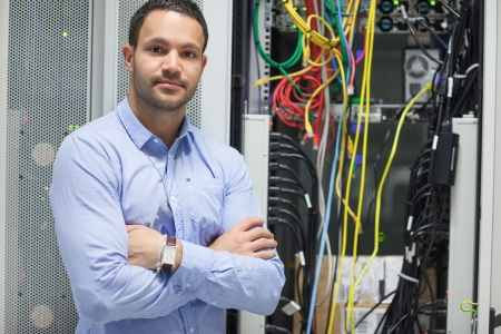 data center: Man standing with arms crossed in data center in front of servers Stock Photo