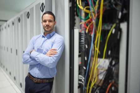 Man leaning against server locker in data center photo