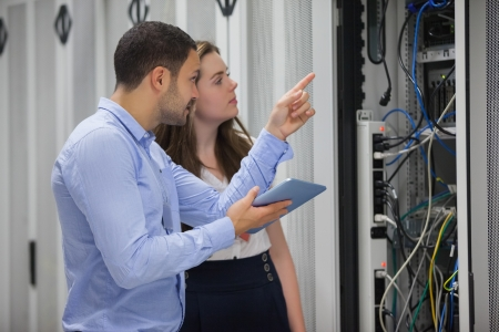 Technicians looking at servers in data center using tablet pc Imagens