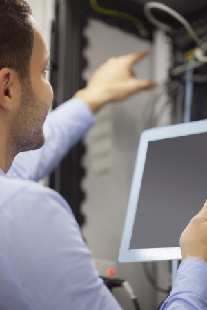 Man fixing wires with tablet pc in data center photo