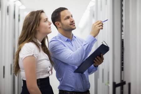 storage facility: Technicians with clipbard looking at servers in data center Stock Photo