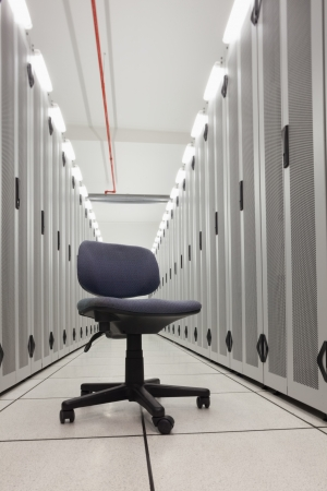 Chair in empty row of servers in data center Stock Photo - 15592816